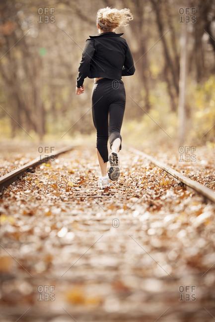 Female runner jogging down train tracks covered in leaves