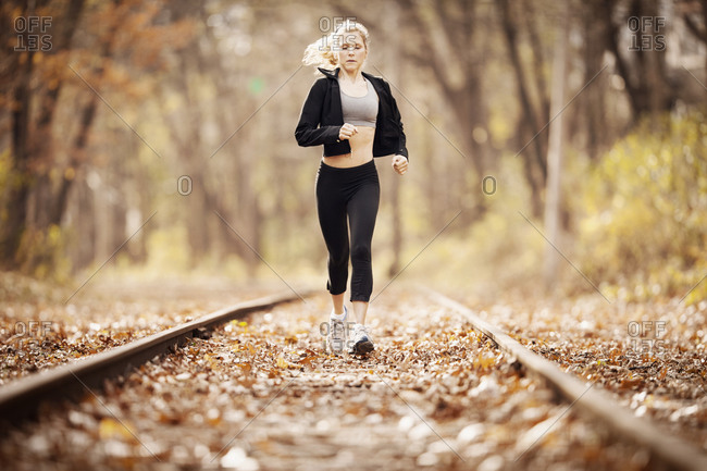 Female runner jogging down train tracks covered in leaves, front view