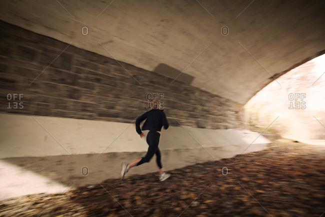 Female runner jogging through tunnel in autumn