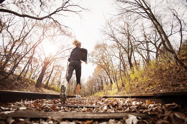 Female runner jogging down train tracks in autumn