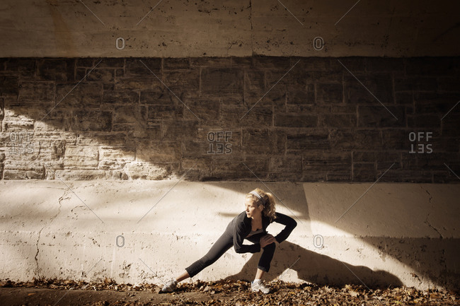 Female runner stretching out legs in a tunnel