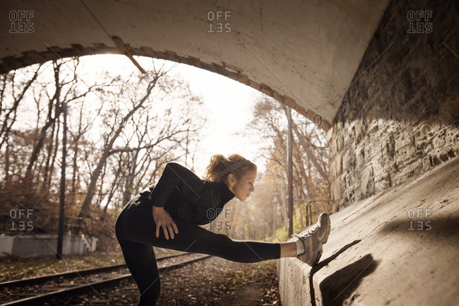 Female runner stretching in a tunnel