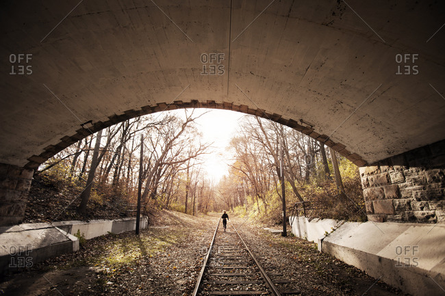 Female runner jogging out of tunnel in autumn