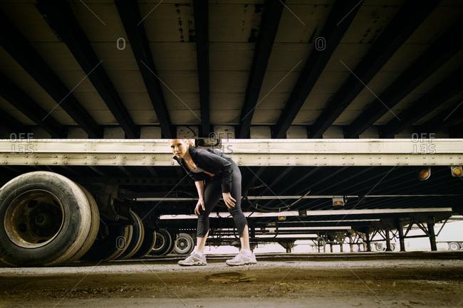 Female runner stretching in between parked semi trucks