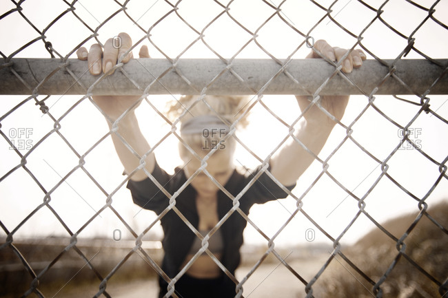 Female runner stretching while up against a fence
