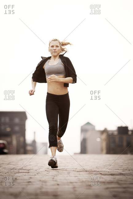 Female runner jogging through town front view