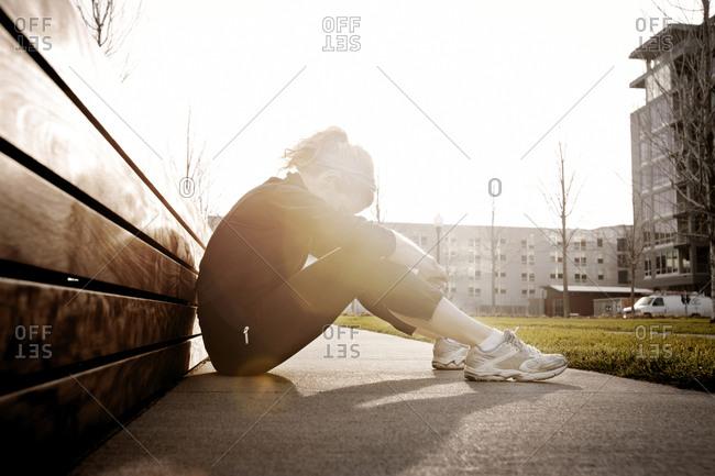 Female runner taking a break on a sidewalk