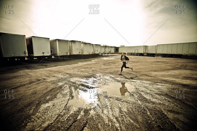 Female runner jogging through muddy semi truck trailer parking lot
