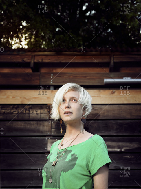 Blonde woman standing outside in front of wooden wall