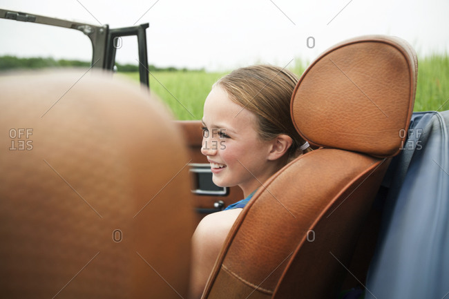 Young girls sitting in passenger seat of convertible