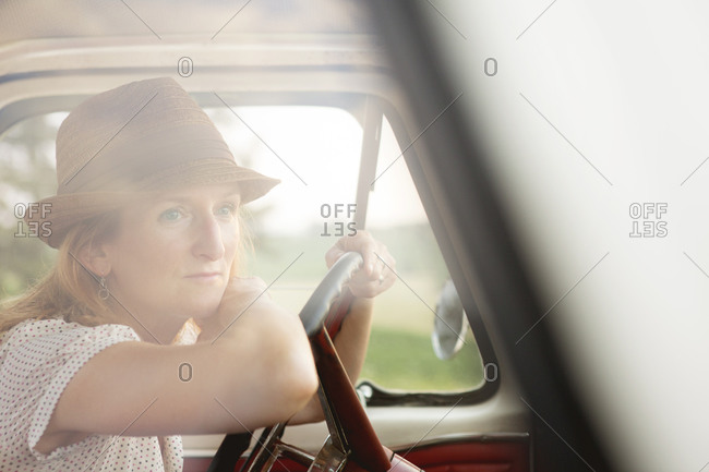 Woman leaning on wheel of old pickup truck at sunset