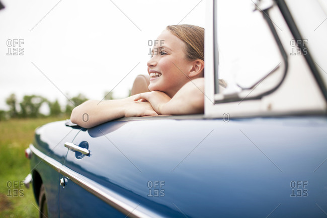Young girls sitting in passenger seat of convertible looking over the edge