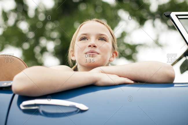 Young girls sitting in passenger seat of convertible looking over the edge close up