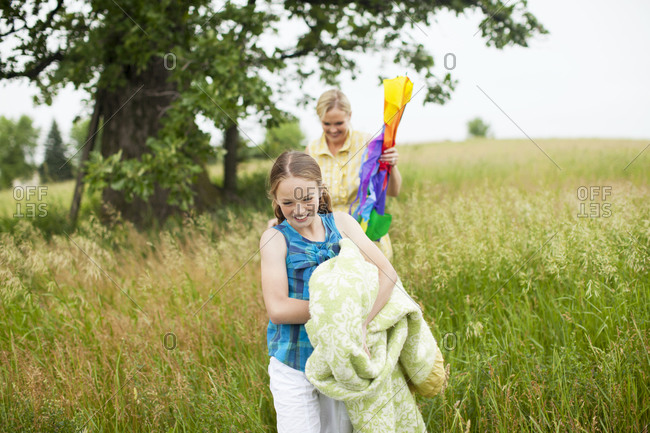 Mother and daughter carrying blanket and kite through field