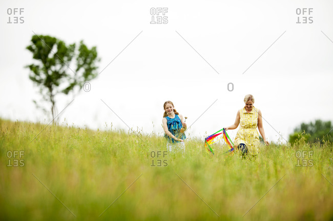 Mother and daughter preparing to fly kite out in field