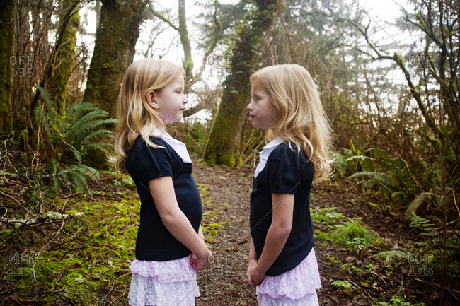 Twin sisters facing each other standing in the rainforest