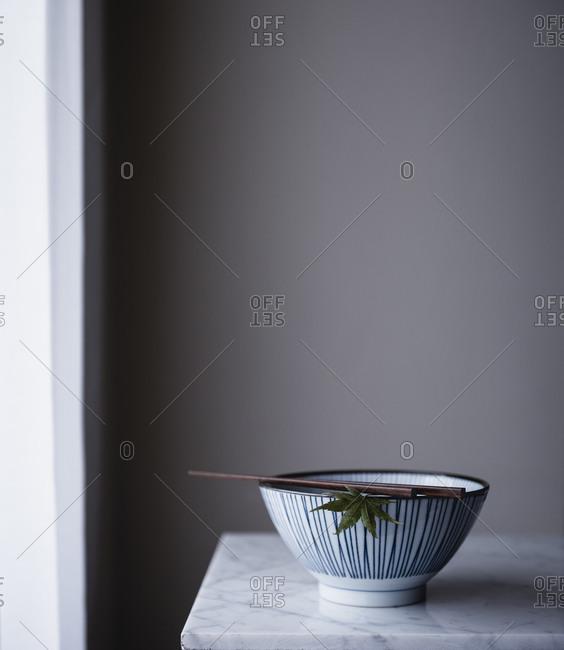 Chopsticks resting on a bowl