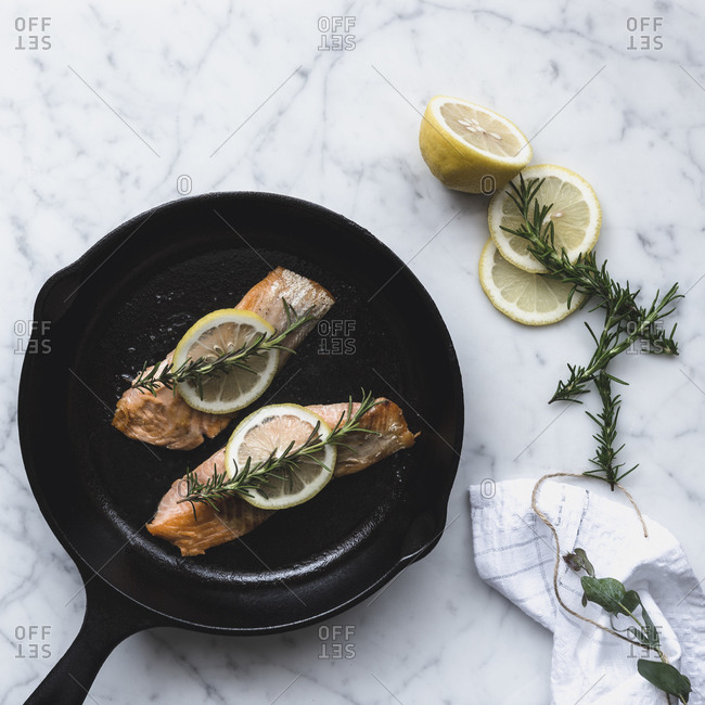 Salmon filets with lemon and rosemary in pan