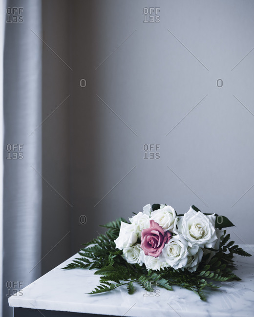 Bouquet of white and pink roses lying on a countertop