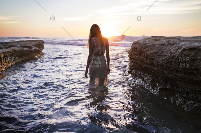 Woman walking in shallow ocean water at sunset