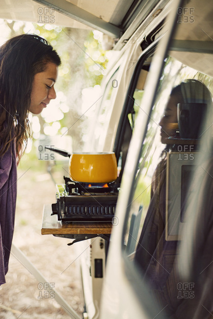 Woman smelling food cooking on a hot plate