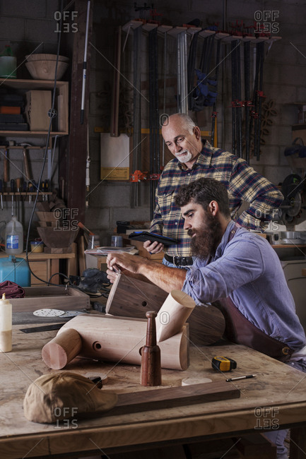 Senior carpenter overlooking junior carpenter work with wood