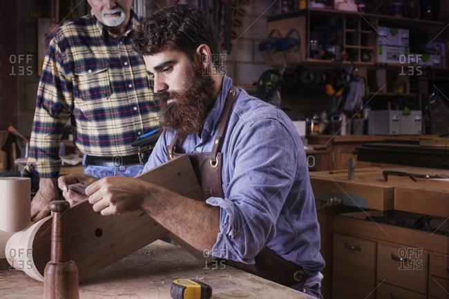 Senior carpenter overlooking junior carpenter while working with wood