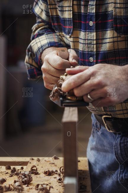 Close up of carpenter shaving wood