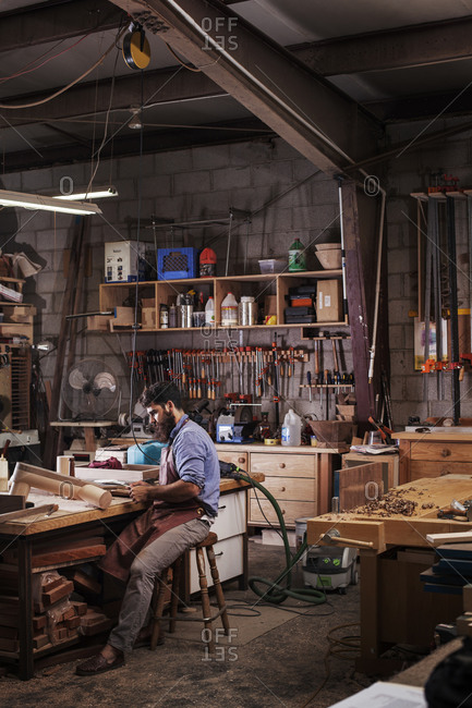 View of carpenter sitting in his workshop