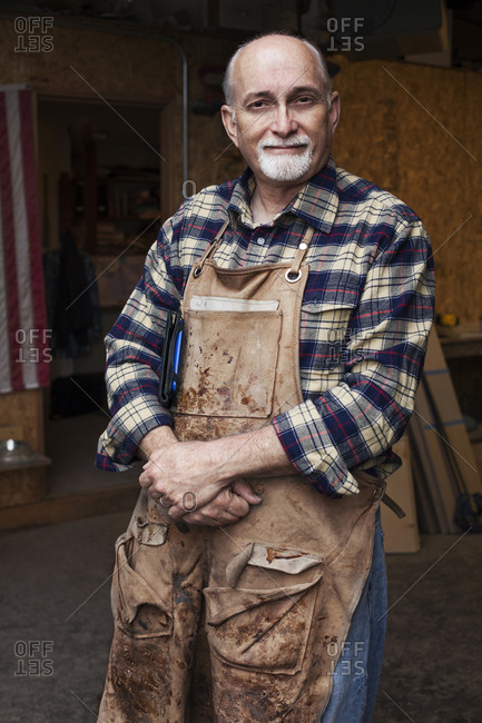 Carpenter standing out in front of his workshop