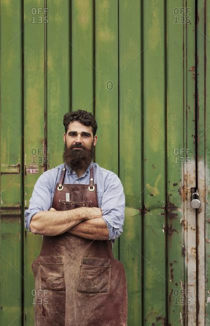 Carpenter standing outside of a workshop