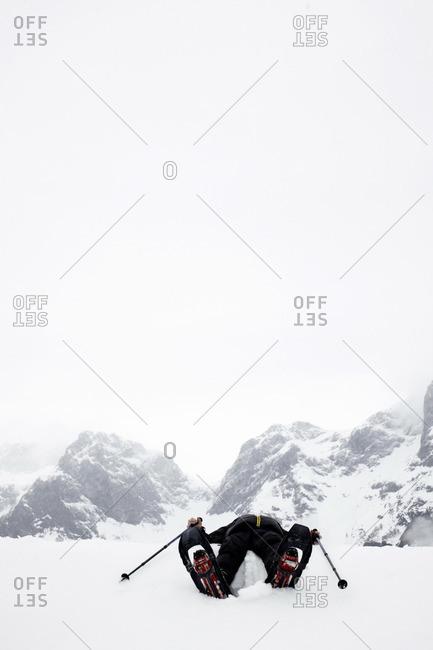 Person wearing snowshoes lying in snow, Sankt Martin am Tennengebirge, Lammertal, Salzburg, Austria