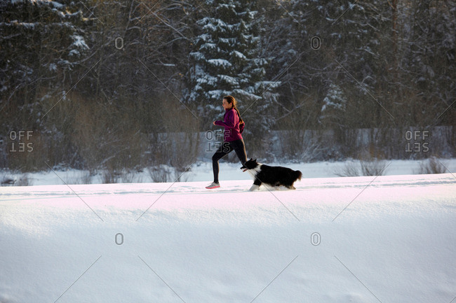 Pullach, Isartal, Bavaria, Germany - April 3, 2011: Runner with dog, in snow at the Isar river in Pullach, Isartal, Bavaria, Germany