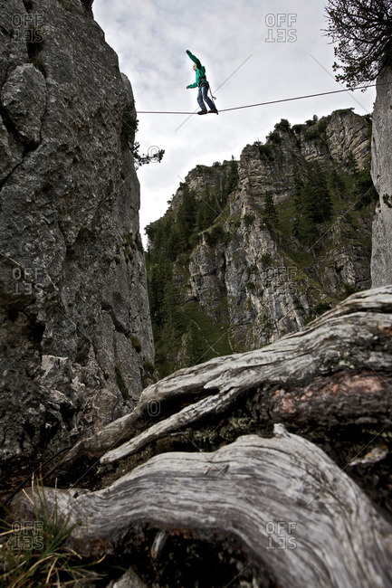 Young man balancing on a highline between two rocks, Oberammergau, Bavaria, Germany