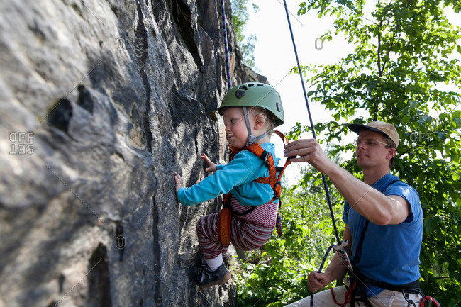 Boy climbing in a quarry with his father, Leipzig, Saxony, Germany