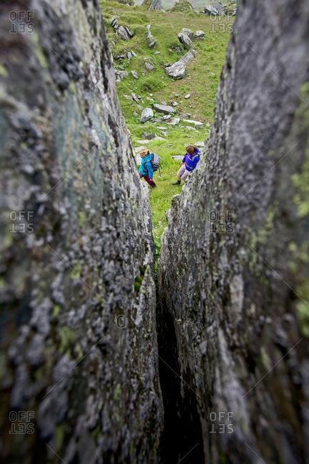 Two female hikers passing a rock crevice, Alpe-Adria-Trail, Nockberge, Carinthia, Austria