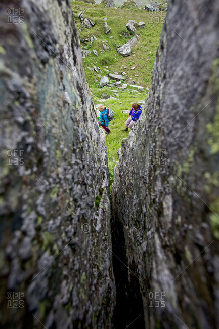 Two female hikers passing a rock crevice, Alpe-Adria-Trail, Nockberge, Carinthia, Austria