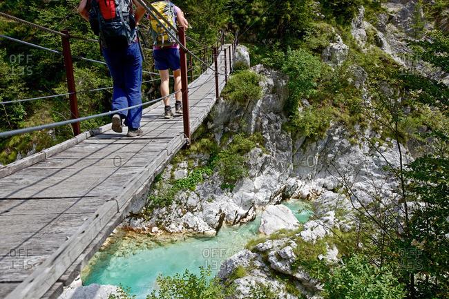 Two female hikers crossing swing bridge above the river Soca, Alpe-Adria-Trail, Tolmin, Slovenia