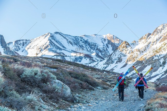 Two skiers carrying their skis on the back, Mammoth Lakes, California, USA