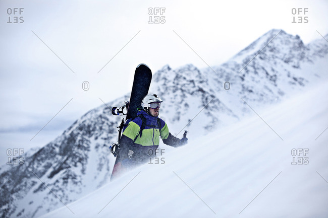 Young snowboarder hiking through the deep powder snow in the mountains, Pitztal, Tyrol, Austria