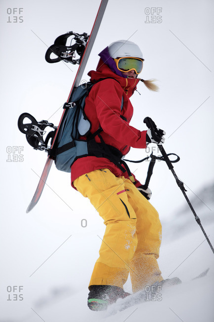 Young female snowboarder hiking through the snow in the mountains, Pitztal, Tyrol, Austria