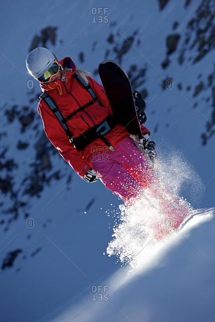 Female snowboarder hiking through the snow in the mountains, Pitztal, Tyrol, Austria