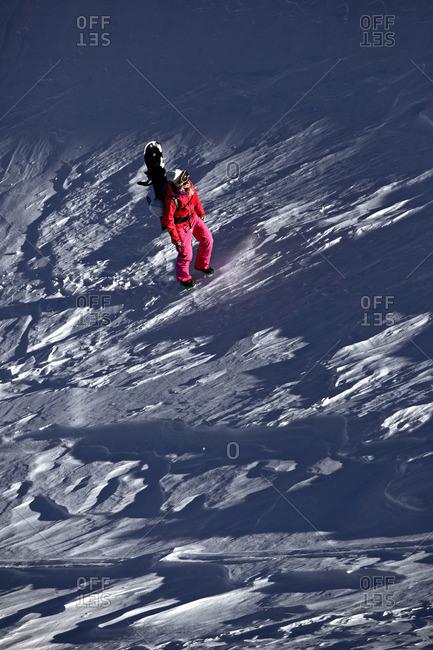 Female snowboarder hiking through deep powder snow in the mountains, Pitztal, Tyrol, Austria