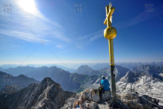 Person sitting beside summit cross of mount Zugspitze, Wetterstein mountain range, Upper Bavaria, Bavaria, Germany