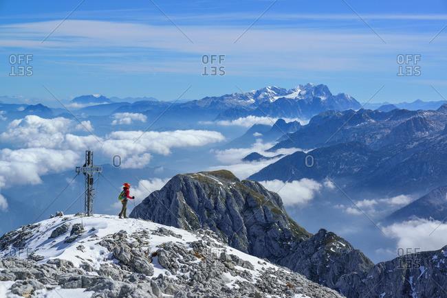 Woman near by summit cross of mount Hoher Goell, Dachstein range in background, Berchtesgaden National Park, Berchtesgaden Alps, Upper Bavaria, Bavaria, Germany