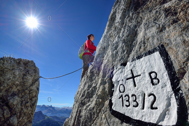 Woman ascending on fixed rope route to Hohes Brett, boundary mark in foreground, Hoher Goell, Berchtesgaden National Park, Berchtesgaden Alps, Upper Bavaria, Bavaria, Germany