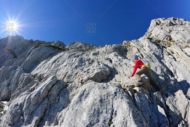 Woman climbing over rock to Hochkalter, Berchtesgaden National Park, Berchtesgaden Alps, Upper Bavaria, Bavaria, Germany