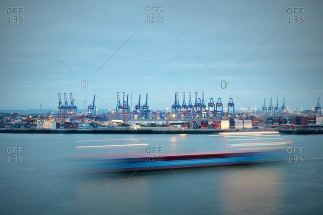 Ship cruising past the port of Hamburg at dawn, view from Docklands, Hamburg, Germany