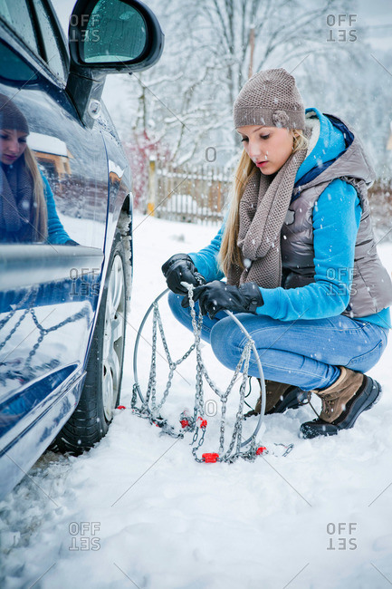Woman applying chain to tire in snow, Styria, Austria