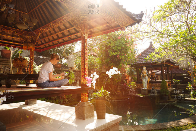 Woman sitting in a pavilion while reading, Ubud, Bali, Indonesia